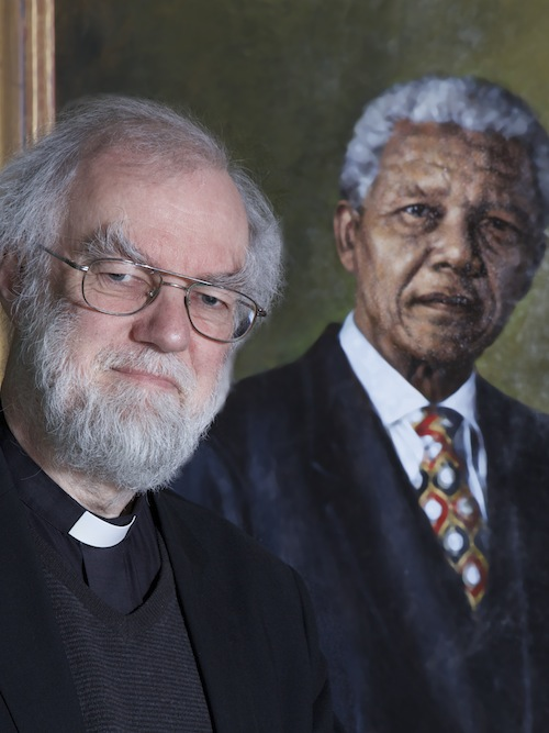 Rowan Williams, Master of Magdalene College and former Archbishop of Canterbury. In front of a portrait of Nelson Mandela who was an honorary Fellow of the College.