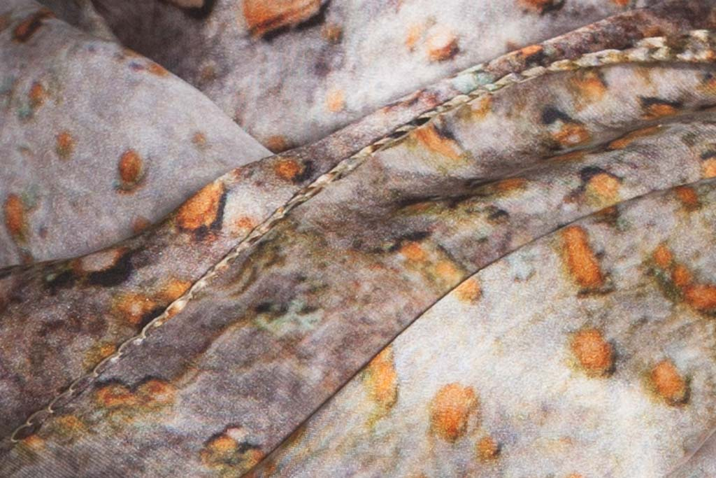 Close-up photograph of Spur Leaf Tree Bark 100% silk scarf by Howard Guest. Silvers with orange dots. Abstract