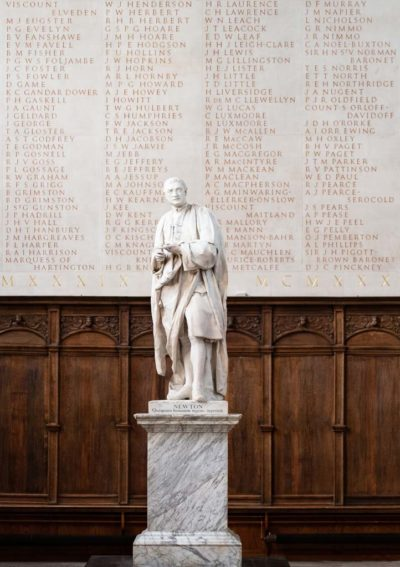 The statue of Isaac Newton in the Antechapel at Trinity College, Cambridge in front of part of the memorial to members of the College who died in WW2.